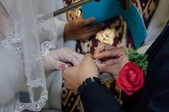 新郎在新娘的手指上把婚戒放 库存照片