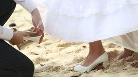 新郎在新娘腿特写镜头上把鞋子放 股票录像
