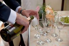 新郎在新婚佳偶前打开一个瓶香槟 新娘和新郎与朋友喝香槟 滑稽的婚姻的片刻 图库摄影