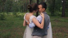 新郎在森林里拿着胳膊的新娘在photoshoot户外 股票录像
