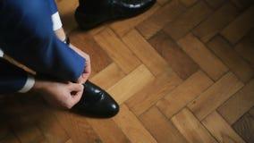 新郎在白色木背景穿鞋子户内 股票视频