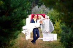 新郎在美丽的湖附近拿着她的胳膊的新娘在森林里 在爱的婚姻的夫妇在婚礼那天 选择聚焦 免版税图库摄影