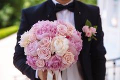 新郎在他的手上的拿着婚礼花束 图库摄影