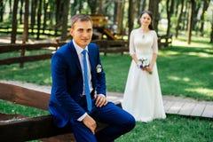 新郎坐木篱芭室外与迷离的秀丽新娘在背景 库存照片