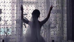 新郎女孩由窗口剪影打开帷幕在屋子里 库存照片