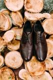 新郎布朗鞋子木背景的 人` s辅助部件 免版税库存图片