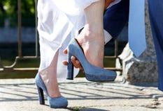 新郎帮助新娘投入她的鞋子 库存图片