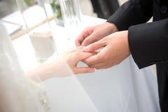 新郎戴着圆环给新娘在婚礼 免版税库存照片