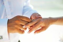 新郎投入圆环 夫妇举行手 婚礼和爱 免版税库存照片