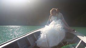 新郎拥抱坐在longtail小船的新娘 股票录像