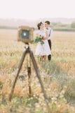 新郎拥抱有婚礼花束后面的新娘,当摆在前面的古板的照相机时 免版税库存照片
