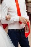 新郎拿着新娘的红色鞋子 库存照片