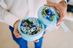 新郎拿着有婚戒的一个圆的箱子与蓝色花 附庸风雅 软的焦点,特写镜头 免版税库存图片