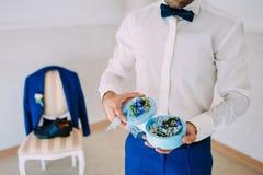 新郎拿着有婚戒的一个圆的箱子与蓝色花 附庸风雅 软绵绵地集中 免版税库存照片