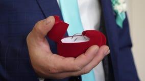 新郎拿着有结婚戒指的箱子在他的提案的手上对他心爱 创建新的家庭 特写镜头 影视素材