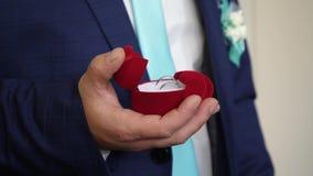 新郎拿着有结婚戒指的箱子在他的提案的手上对他心爱 创建新的家庭 特写镜头 股票视频