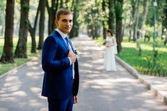 新郎拿着他的夹克衣领室外与迷离的新娘在背景 免版税库存图片