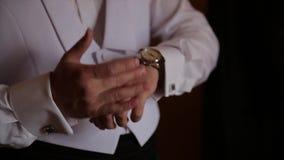 新郎握在领带的手,婚姻衣服 关闭一个手人怎么佩带白色衬衣和链扣 在白色的背景商业查出的人 股票录像