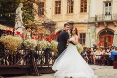 新郎握新娘摆在一个木街道咖啡馆后的` s腰部 库存照片