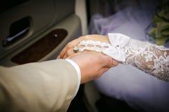 新郎握新娘的手,从大型高级轿车出来 库存照片