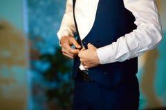 新郎早晨准备,英俊的新郎换衣服和为婚礼做准备,夹克被放置 免版税库存照片