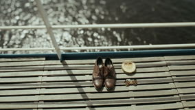 新郎早晨 在一个木地板上的鞋子 蓝色详细资料花袜带系带婚礼 新郎辅助部件 新郎鞋子 水在背景中 股票录像