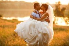 新郎是拿着和亲吻他的背景evenin的新娘 库存图片