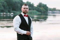 新郎的一张背心、水平的画象,画象在自然背景,河和码头的年轻时髦的人 免版税库存照片