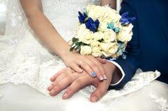 新郎的手在新娘的手上有美丽的新娘花束的在手上 免版税库存照片