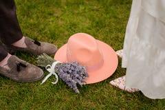 新郎的构成和新娘腿、淡紫色帽子和花束  库存图片