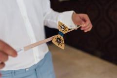 新郎的男性手拿着一根橡皮筋的一只蝴蝶 免版税库存照片