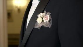 新郎的美丽的钮扣眼上插的花黑燃烧物的在一婚礼那天 股票视频