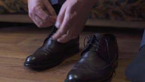 新郎穿鞋子户内 英俊的人男性画象  五颜六色的婚礼衣裳的美丽的式样男孩 人是 股票视频