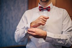 新郎紧固在一件衬衣的袖子的一个按钮有一只红色蝴蝶的在他的脖子 免版税库存图片