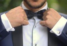 新郎蝶形领结举行黑色衣服 免版税图库摄影