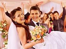 新郎运载在他的手上的新娘 免版税库存图片