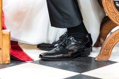 新郎鞋子在婚礼那天在教会里 免版税库存照片