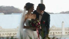 新郎轻轻地亲吻美好的深色的新娘关闭  愉快的新婚佳偶 爱恋的夫妇在都市风景背景关闭  股票视频