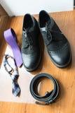 新郎` s和婚姻辅助部件的dog's 淡紫色脖子领带和一双黑皮带和黑鞋子在木背景 免版税库存图片