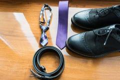 新郎` s和婚姻辅助部件的dog's 淡紫色脖子领带和一双黑皮带和黑鞋子在木背景 免版税库存照片