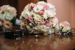 新郎` s婚礼辅助部件 穿上鞋子花、链扣、婚姻的钮扣眼上插的花和传送带花束  库存图片