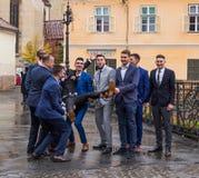 新郎` s朋友在小正方形的教会前面拿着他 锡比乌市在罗马尼亚 免版税库存图片