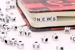 新闻在一个白色块措辞写在书 免版税库存图片