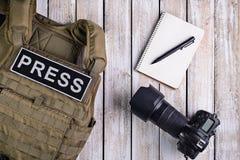 新闻工作者、笔记本和照相机的身体装甲 库存照片