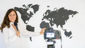 新闻工作者报告关于一张大地图的背景  免版税图库摄影
