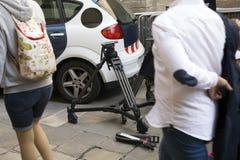 新闻工作者摄象机的三脚架在街道上的 免版税库存照片
