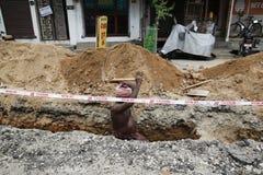 新闻纪录片的社论图象 小组有铁锹的工作者在沟槽,开掘沿路掘沟 免版税库存照片