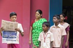 新闻纪录片的社论图象 有制服的年轻人在学校读报纸 库存图片