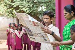 新闻纪录片的社论图象 有制服的年轻人在学校读报纸 免版税库存图片