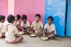 新闻纪录片的社论图象 未认出的孩子吃午餐在军用餐具 图库摄影